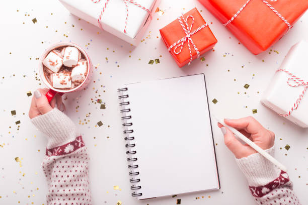 Woman with notepad, cacao and Christmas presents Cozy holidays. Woman with notepad, cacao and Christmas presents on white background, copy space list stock pictures, royalty-free photos & images