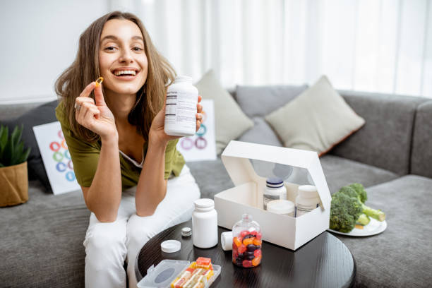 Woman with nutritional supplements at home Portrait of a young smiling woman taking nutritional supplements at home. Concept of biohacking and preventive medicine biohacking stock pictures, royalty-free photos & images