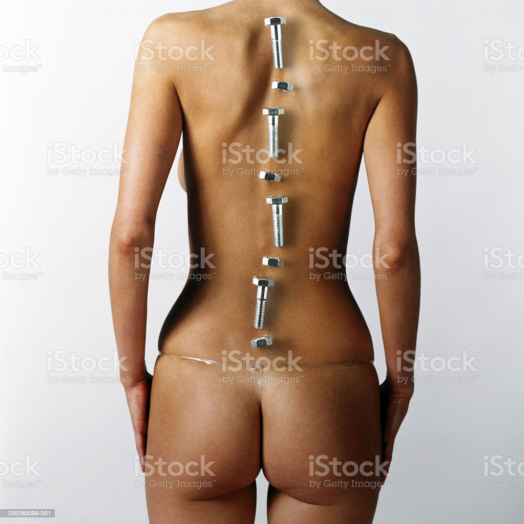 Woman with nuts and bolts placed over line of backbone, rear view stock photo
