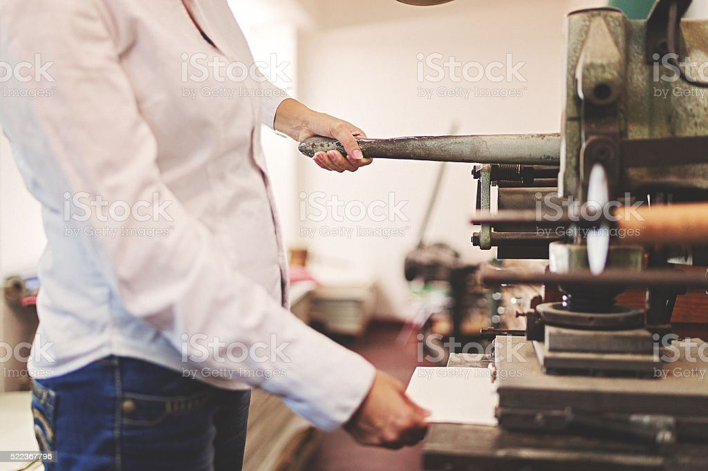 Woman with old machine for hot stamping stock photo