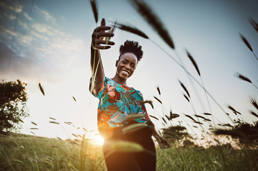 Afro American woman with open arms breathing in the nature