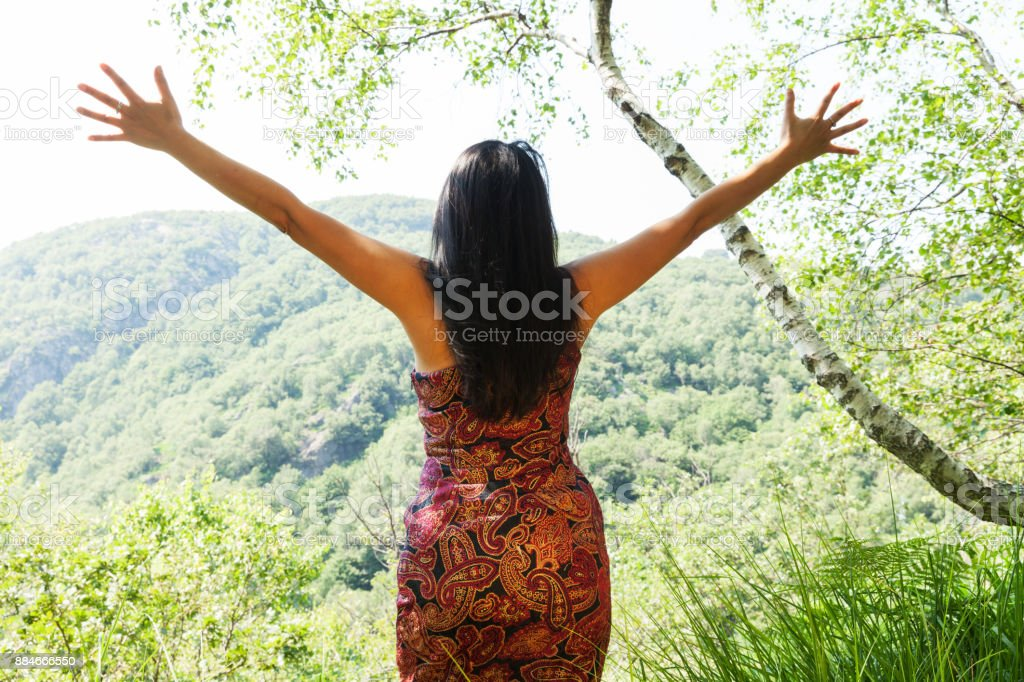 woman with open arms in the forest, concept stock photo