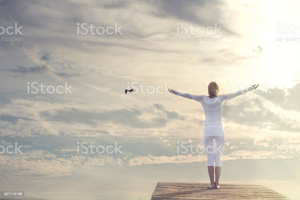 woman with open arms meditating in front of a spectacular sky stock photo