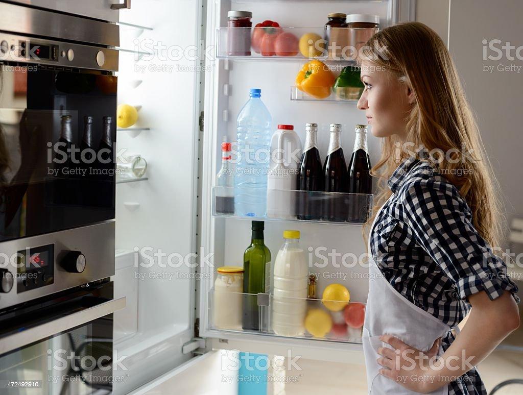 Woman with open fridge stock photo