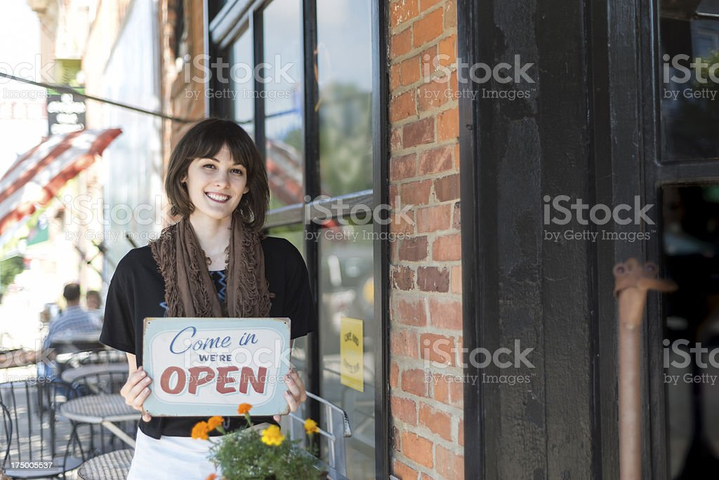 Woman with open sign in front of cafe in Chelsea royalty-free stock photo