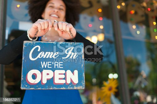 Woman holding vintage open sign up outside of a boutique store front. Photograph taken in Grand Rapids, Michigan.