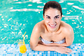 istock Woman  with orange juice in the swimming pool 185222707