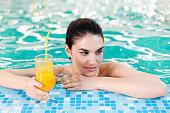 istock Woman  with orange juice in the swimming pool 185250240