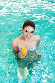 istock Woman  with orange juice in the swimming pool 186841854
