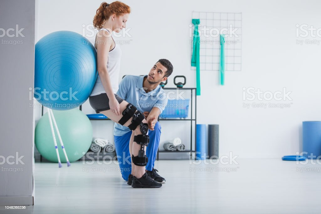 Woman with orthopedic problem exercising with ball while physiotherapist supporting her stock photo