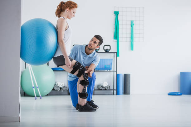woman with orthopedic problem exercising with ball while physiotherapist supporting her - physical therapy zdjęcia i obrazy z banku zdjęć