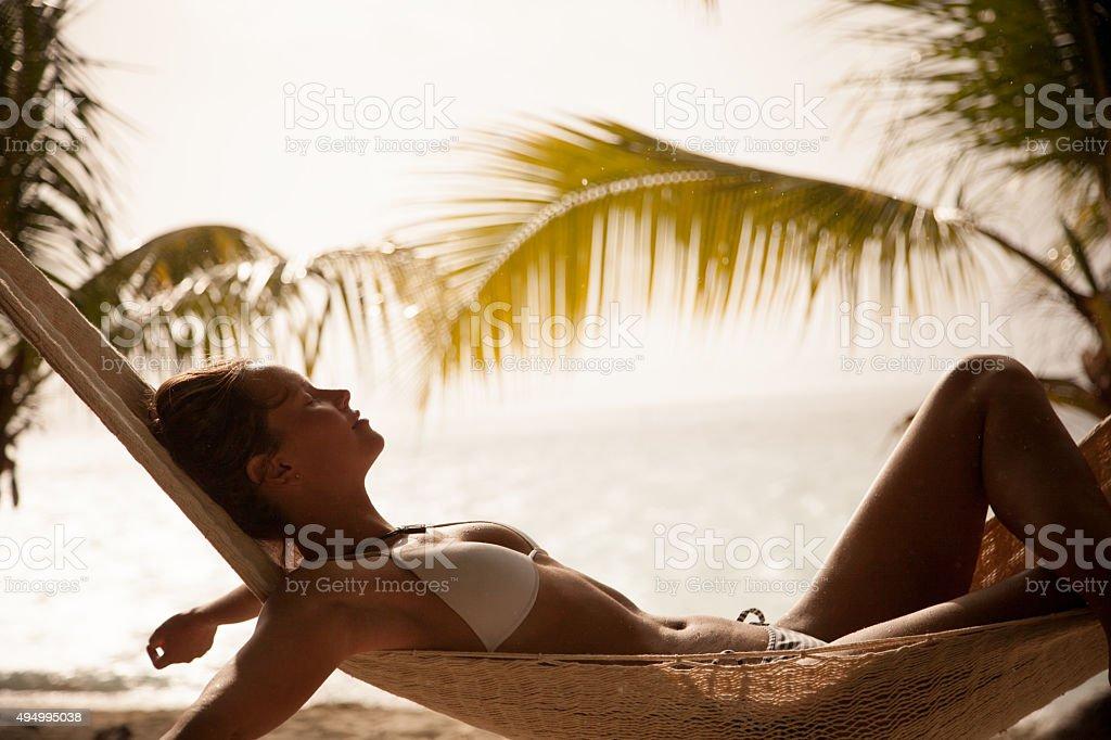 Mulher com os braços esticados Relaxando na rede na praia - foto de acervo