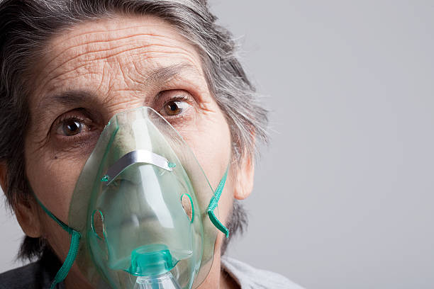 Woman with oxygen mask Portrait of senior woman wearing an oxygen mask, with copy space to the right   oxygen mask stock pictures, royalty-free photos & images