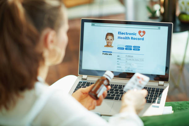 woman with pack of pills and medicine bottle checking ehr stock photo