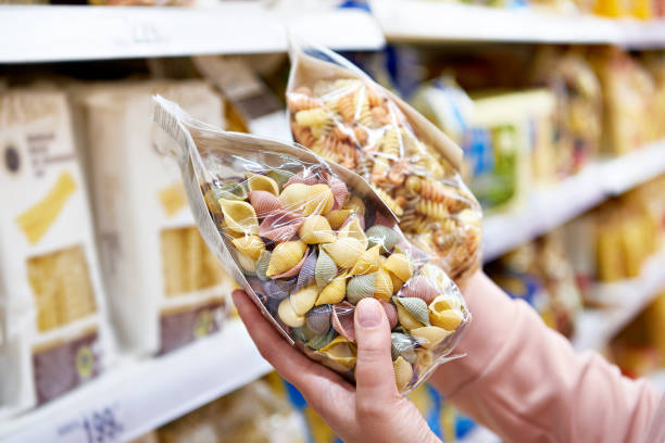 Woman with package pasta in shop stock photo