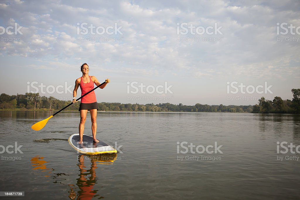 Woman with paddle stands on paddleboard in water stock photo