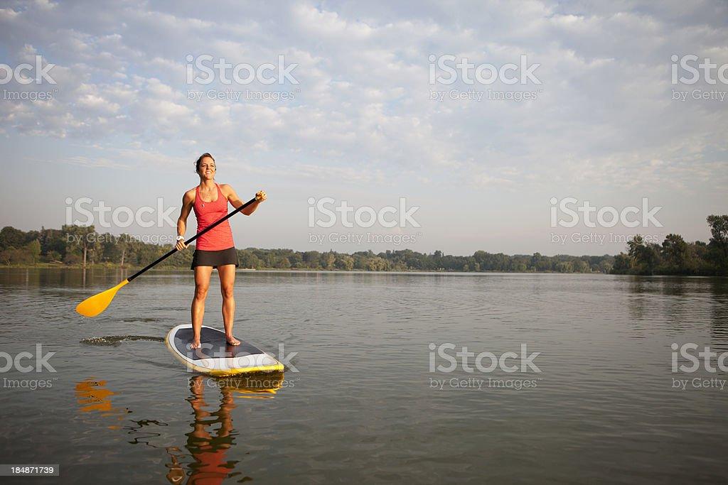 Женщина с гребли стоит в воде на Гребная доска для сёрфинга стоковое фото