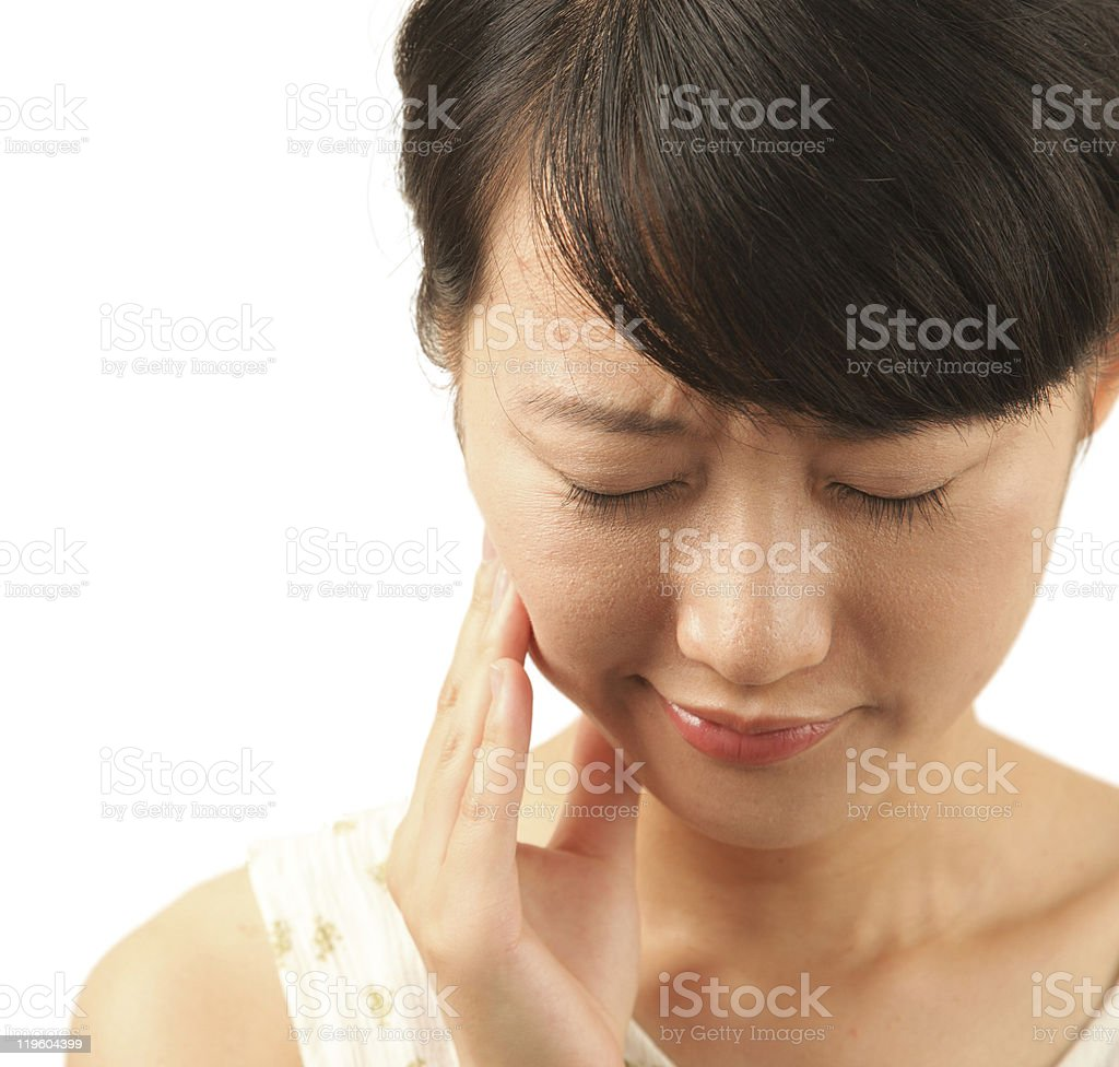 Woman with painful facial expression holding cheek stock photo