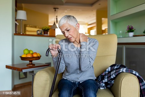 istock Woman with Pains Grey Hair Sitting in Armchair 1194374570