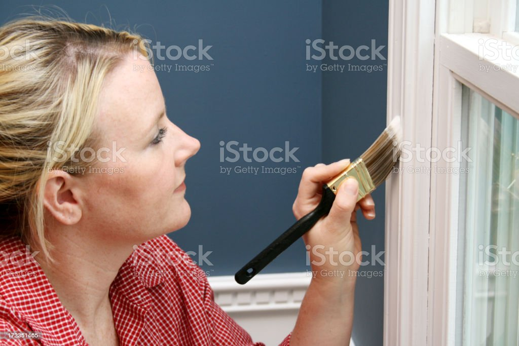 Woman with paintbrush painting a window white royalty-free stock photo