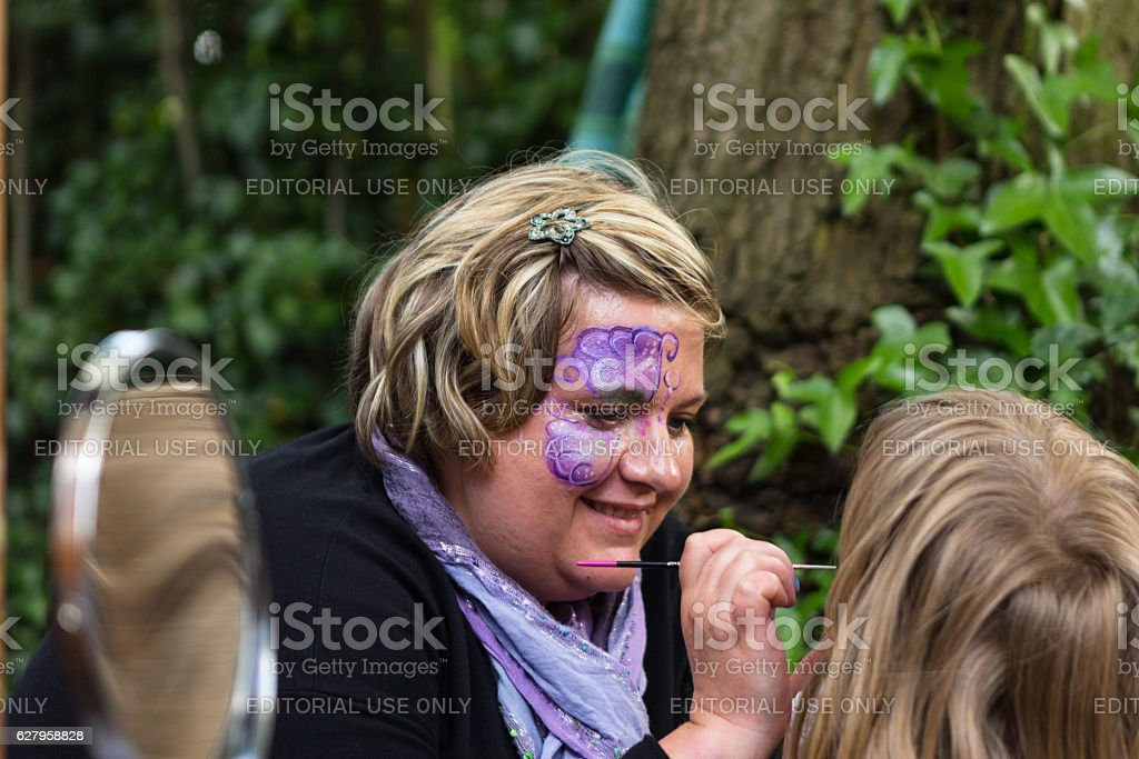 Woman with painted face painting faces at event stock photo