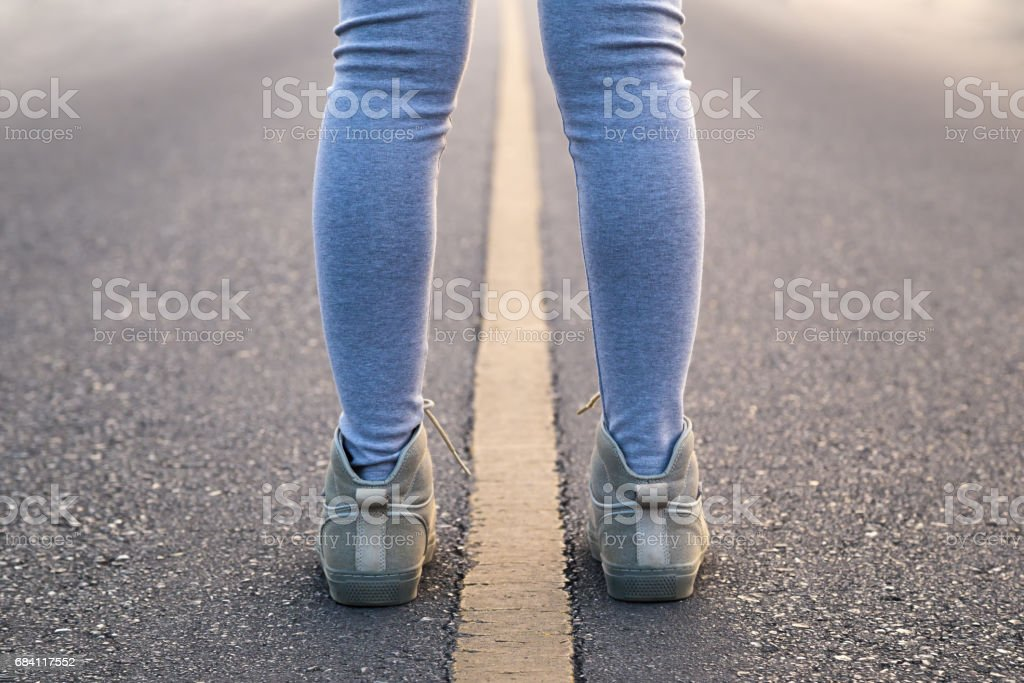 A woman with pair of legs stand astride line road for a exercise in the morning. foto stock royalty-free