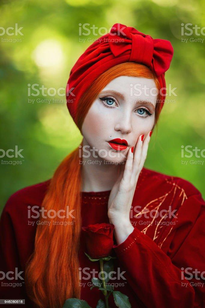 f655fb7a0e6dd3 Een vrouw met bleke huid en lange rode haren een rode jurk en een tulband op