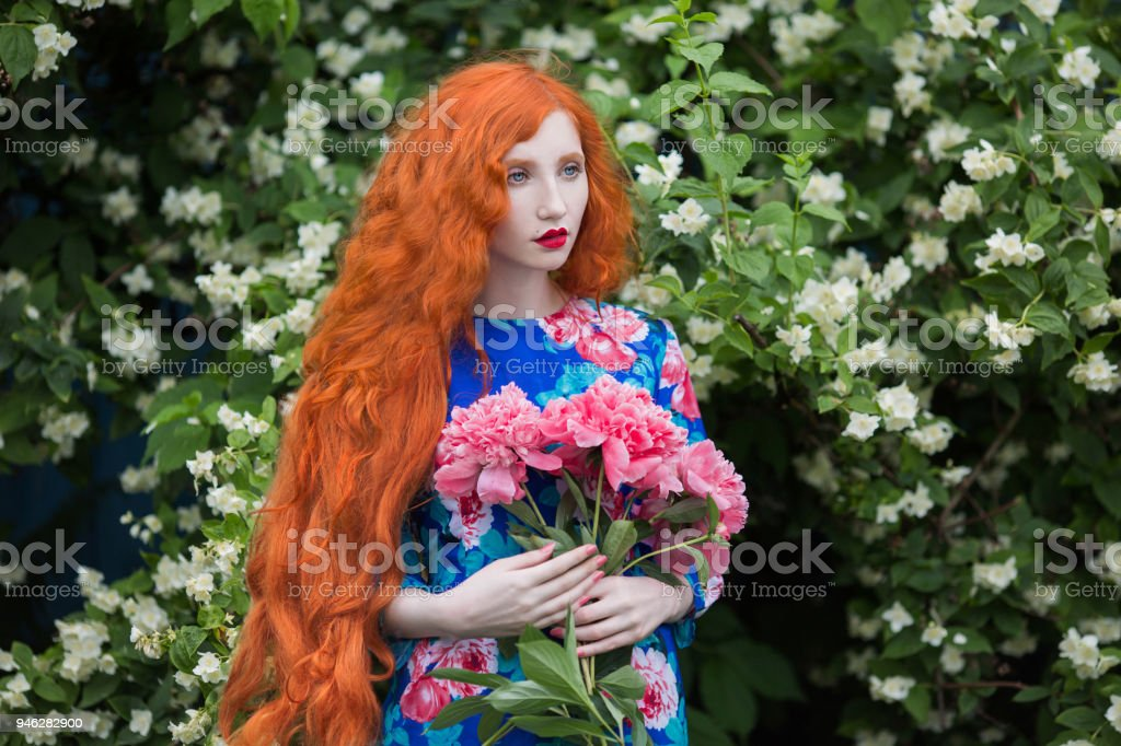 Woman With Pale Skin And Long Red Hair In Peony Dress On Background