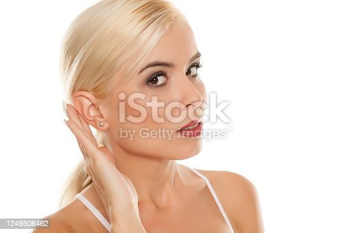 Portrait of beautiful blonde woman on white background with palm behind her ear