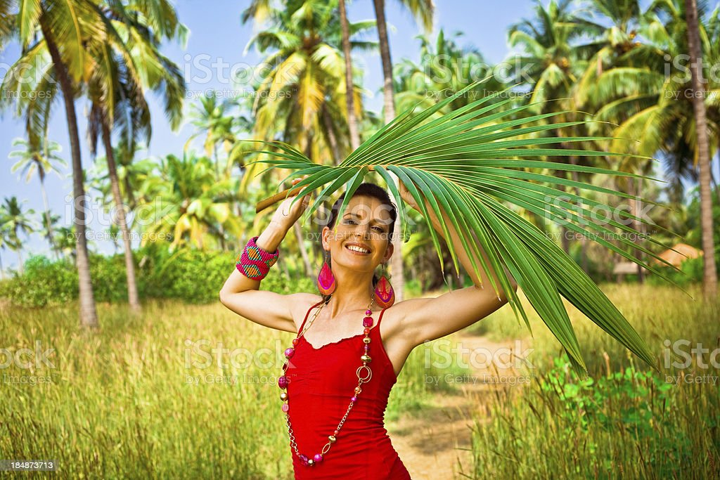 Woman with palm leaf Happy woman on tropical vacation holding palm leaf above her head, smiling at the camera. Coconut palm trees in the background. 30-34 Years Stock Photo