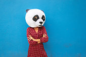 Woman with panda mask against blue wall