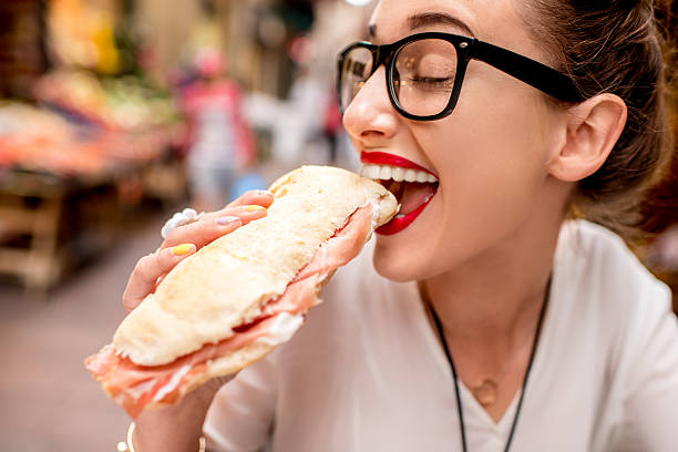 Woman with panini Young woman sitting with panini sandwich with prosciutto at the cafe outdoor on the street in Bologna city female sandwich stock pictures, royalty-free photos & images