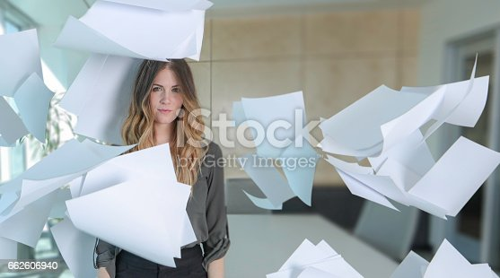 Woman with paper all around her in conference room