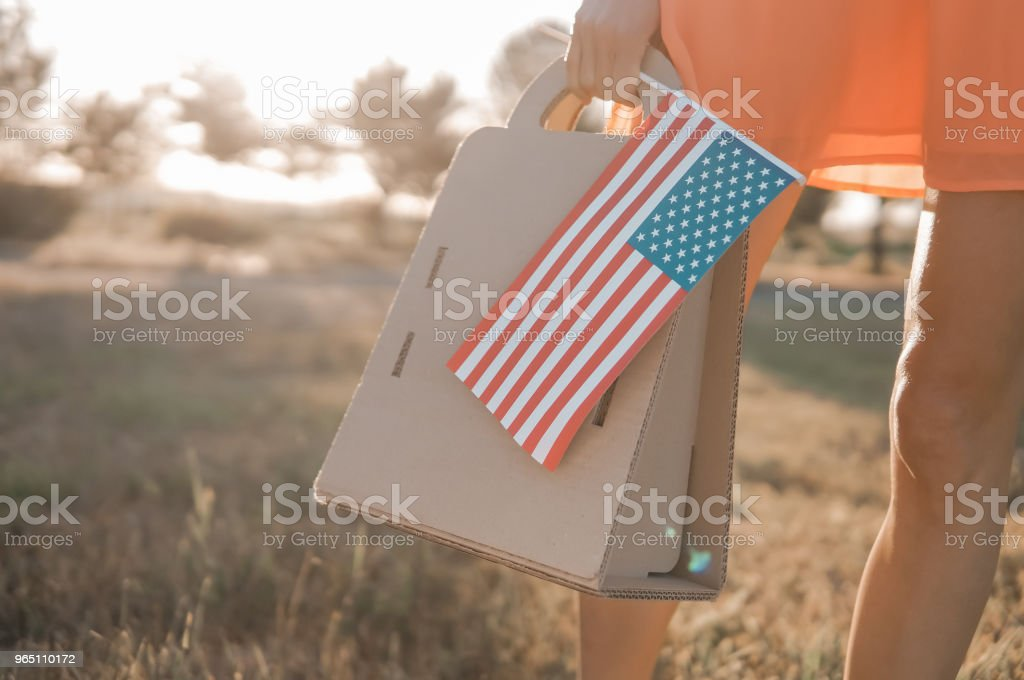 Woman with paper bag and american flag during sunset zbiór zdjęć royalty-free