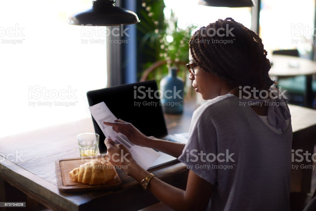 Woman with papers Young black woman with eyeglasses holding paper documents. Laptop computer and croissant are on the table. Adult Stock Photo