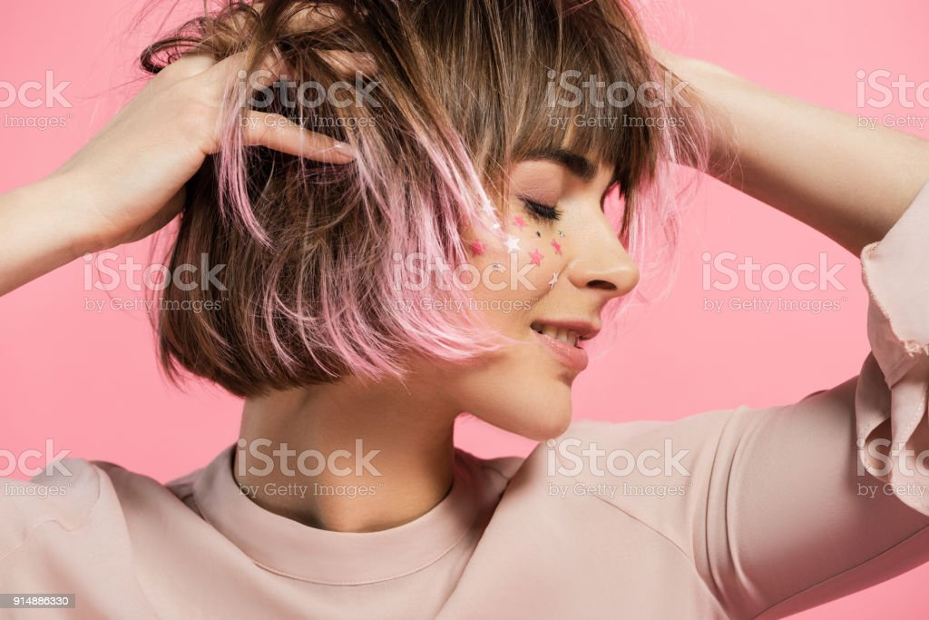 woman with party makeup and pink hair stock photo
