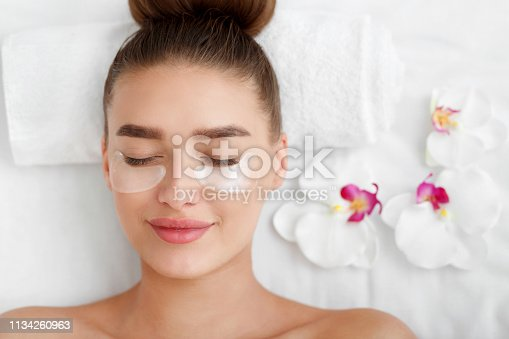 istock Woman with patches under eyes, relaxing in spa center 1134260963