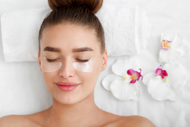 woman with patches under eyes, relaxing in spa center - abaixo imagens e fotografias de stock