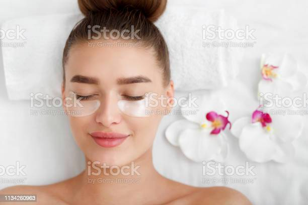 Photo of Woman with patches under eyes, relaxing in spa center