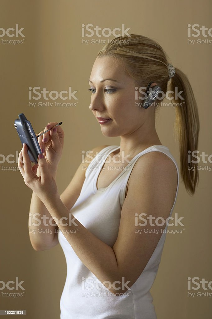 woman with PDA and wireless head set royalty-free stock photo