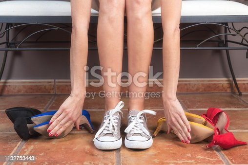 istock Woman with perfect slim legs, choosing comfortable sneakers rather than uncomfortable high heels shoes. 1132753443