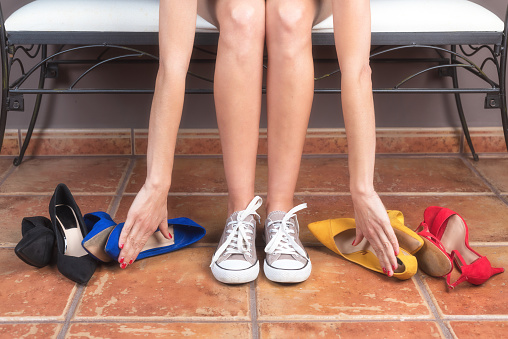 istock Woman with perfect slim legs, choosing comfortable sneakers rather than uncomfortable high heels shoes. 1132753679