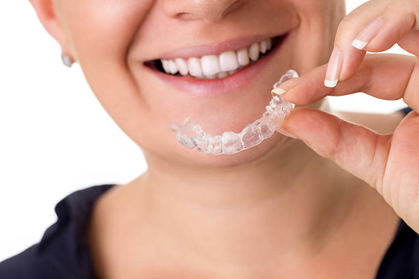 Woman with perfect teeth holding invisible braces stock photo