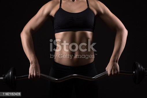 Woman with perfectly trained body is exercising on a barbell. Fitness, workout and training concept.