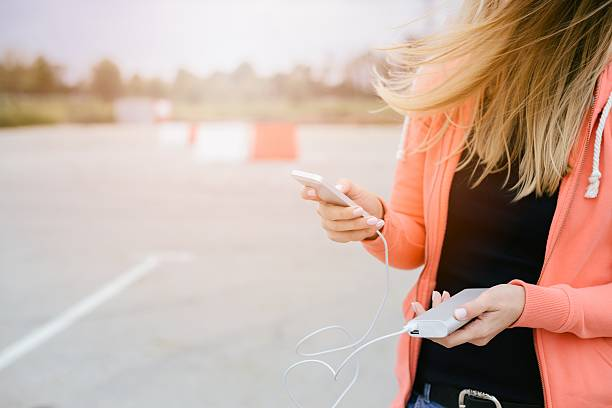 Woman with phone and power bank playing the mobile games Woman with phone and power bank playing the smartphone mobile games. Woman playing mobile games on smartphone on the street battery charger stock pictures, royalty-free photos & images