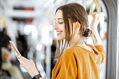 Close-up portrait of a young woman using smartphone while standing in the modern tram