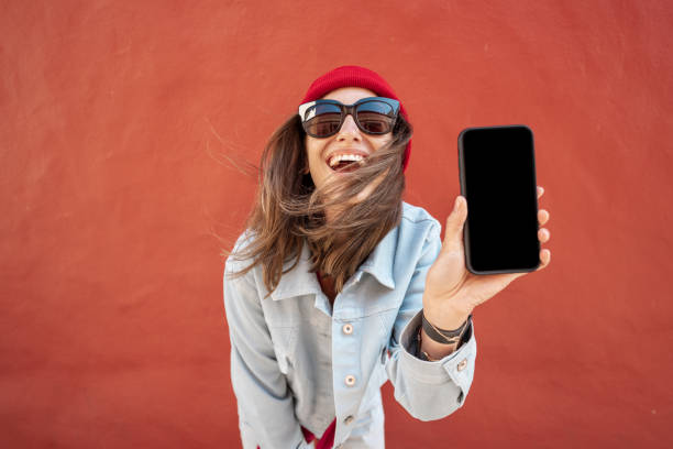 Woman with phone on red background stock photo