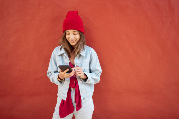 Woman with phone on the red background outdoors stock photo