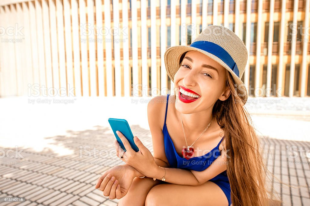 Woman with phone outdoors stock photo
