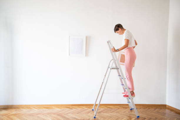 woman with picture frame standing on the ladder - curator stock pictures, royalty-free photos & images